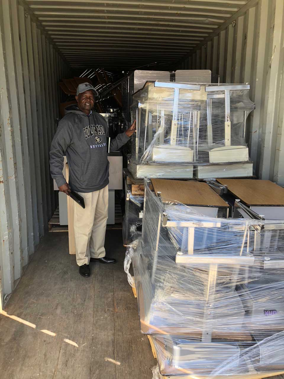 Philemon-with-desks-and-other-school-supplies-in-container-for-Onjinyo-Kenya